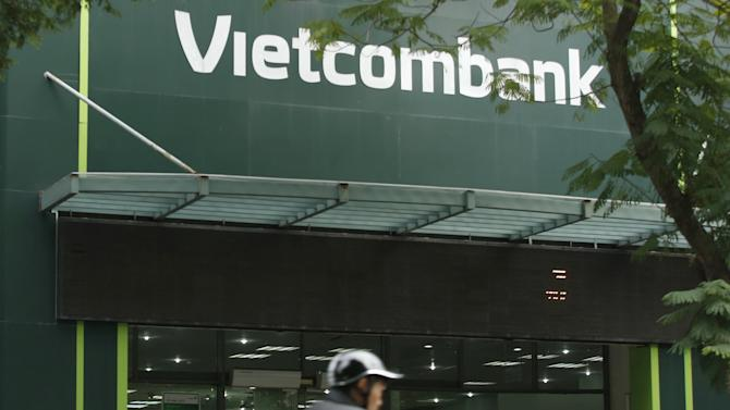 A motorcyclist rides past a branch of Vietcombank in Hanoi, Vietnam