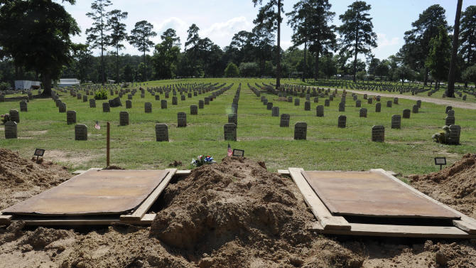 This photo taken June 12, 2013 shows empty and recently filled graves in the Joe Byrd Cemetery in Huntsville, Texas. The cemetery, commonly known as Peckerwood Hill, contains the remains of unclaimed Texas prison inmates. (AP Photo/Pat Sullivan)