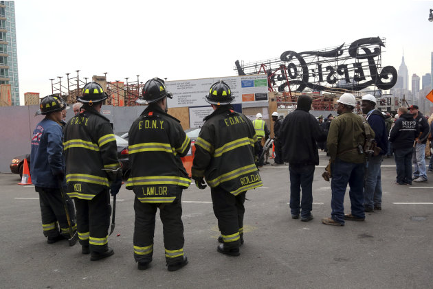 "Firefighters, police officers and construction workers work the scene of a crane collapse at a construction site in the Queens borough of New York, Wednesday, Jan. 9, 2013, behind a big neon ""Pepsi Co"