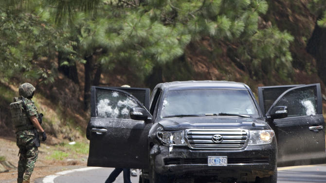 An armored U.S. Embassy vehicle is checked by military personal after it was attacked by unknown assailants on the highway leading to the city of Cuernavaca, near Tres Marias, Mexico, Friday, Aug. 24, 2012. Two U.S.  government employees were shot and wounded in an attack on their vehicle south of Mexico City on Friday, a law enforcement official said. (AP Photo/Alexandre Meneghini)