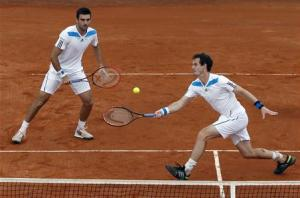 Britain's Murray returns a ball as his teammate Fleming looks on during their Davis Cup quarter-final doubles tennis match against Italy in Naples