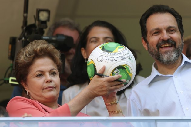 Brazil's President Rousseff shows her autograph on a soccer ball as she stands beside Brasilia's Governor Queiroz during the inauguration of the National Mane Garrincha Stadium in Brasilia
