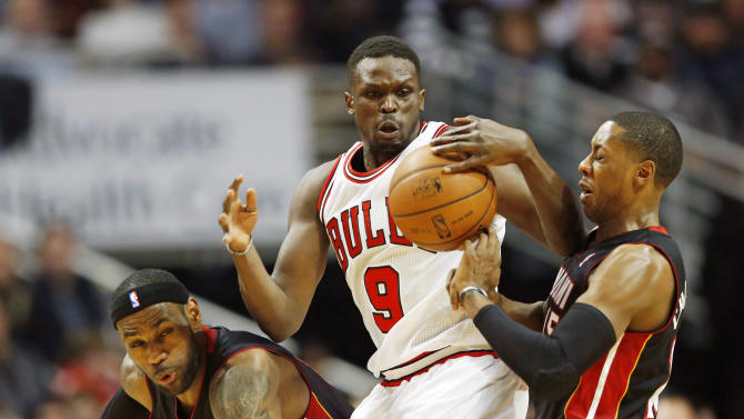 Chicago Bulls forward Luol Deng, center, tries to control the ball against Miami Heat forward LeBron James, left, and guard Mario Chalmers, right, during the first half of an NBA basketball game in Chicago, Thursday, Dec. 5, 2013. (AP Photo/Kamil Krzaczynski)