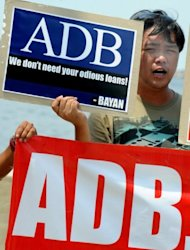 File photo of Filipino protesters displaying mock Asian Development Bank (ADB) placards during a protest against the 45th Annual Meeting of the Board of Governors of the ADB in Manila in May. The bank has warned of significant risks caused by the effects of the European debt crisis and continued weakness in the United States, both of which are major export markets