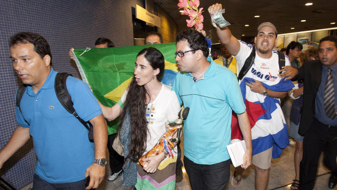 Cuban dissident blogger Yoani Sanchez, center, is chanted at by pro-Castro supporters, accusing her of being a U.S. spy, upon her arrival at the Guararapes International airport, in Recife, Brazil, Monday, Feb.18, 2013. Sanchez has arrived in Brazil - her first stop in a three-month tour of 12 nations. Sanchez was barred from leaving Cuba for the last decade. But she's taking advantage of the communist island's relaxation on travel restrictions. (AP Photo/Hans von Manteuffeul-Agencia O Globo)