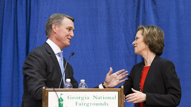 "FILE - This Oct. 7, 2014, file photo shows Georgia Democratic candidate for U.S. Senate Michelle Nunn and Republican candidate David Perdue talking after their debate in Perry, Ga. In an arena usually reserved for rodeos and livestock shows, Nunn told the boisterous crowd she was ""glad to be home."" Purdue stood on the same debate stage and bellowed: ""Welcome to Perdue country."" Neither candidate lives near the fairgrounds, much less among cattle or row crops. But both candidates have made a concerted play for rural and small-town voters. (AP Photo/David Goldman, File)"