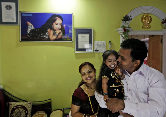 Unidentified relatives congratulate Jyoti Amge, 18, who stands at 61.95 centimeters (2 feet) at her residence before a press conference with Guinness World Records in Nagpur, India, Friday, Dec. 16, 2