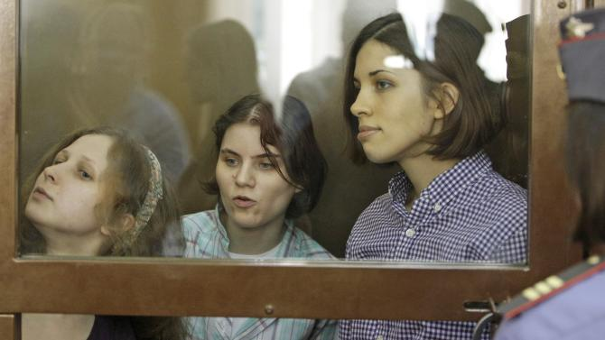 """From left, Yekaterina Samutsevich, Maria Alekhina, Nadezhda Tolokonnikova, members of feminist punk group Pussy Riot sit behind bars at a court room in Moscow, Russia,  Russia, Monday, July 30, 2012.Three members of the band are facing trial for performing a """"punk prayer"""" against Vladimir Putin from a pulpit of Moscow's main cathedral before Russia's presidential election in March, in which he won a third term. (AP Photo/Mikhail Metzel)"""