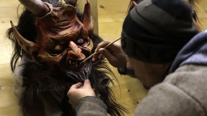 Wood carver Hans Schwabl (26) paints at a traditional wooden Perchten mask in his factory in Inzell, southern Germany, Thursday, Nov. 27, 2014. The masks are made for the upcoming Saint Nicolas Buttnmandl and Perchten parades in November and December around the Alp regions, in southern Germany and Austria. During the Buttnmandl parades, unmarried men, known as Buttnmandl and Krampusse, are dressed in straw or skins with wooden masks or skins over their heads and large cow-bells tied around their hips to make loud noises. They follow Saint Nicholas from house to house on December 5 and 6 every year to bring luck to the good ones and punish the idles. The Perchten parades take place after Christmas. (AP Photo/Matthias Schrader)