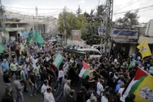 Mourners carry the body of 22-year-old Palestinian…