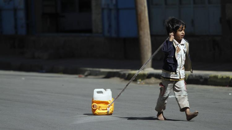 A boy drags a jug of water, joining other children on their daily search for potable water in Sanaa