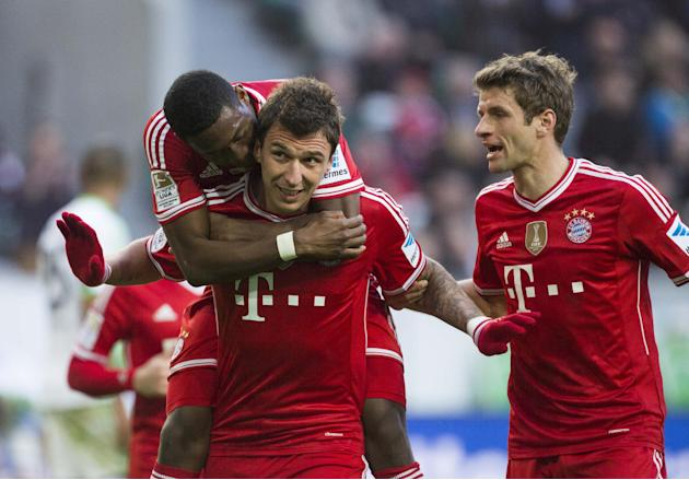 Bayern's Mario Mandzukic of Croatia, center, celebrates  after scoring his side's 3rd goal with Bayern's David Alaba of Austria, left, and Bayern's Thomas Mueller, right, during the Ge