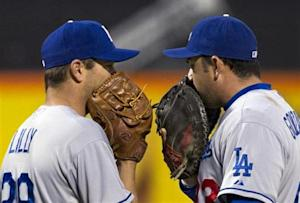 Los Angeles Dodgers' Ted Lilly talks with first baseman Adrian Gonzalez while pitching to New York Mets in MLB game in New York