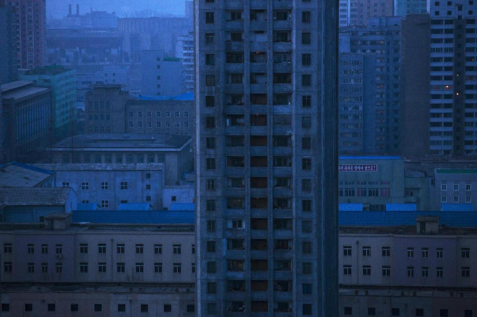 An apartment block stands among the buildings at dawn in central Pyongyang, North Korea, Wednesday, April 10, 2013. (AP Photo/David Guttenfelder)