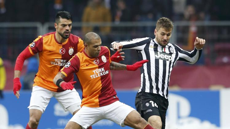 Llorente of Juventus challenges Melo and Zan of Galatasaray during their Champions League soccer match in Istanbul