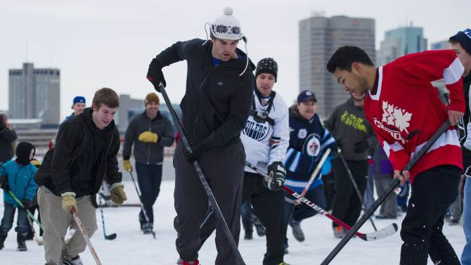 Winnipeg Jets captain Andrew Ladd, center, plays street hockey with hockey fans and a few fellow NHL players atop a parking garage at the Forks in Winnipeg, Manitoba, on Tuesday, Nov. 13, 2012. The lockout between the NHL and the players is in it's 59th day. (AP Photo/The Canadian Press, David Lipnowski)