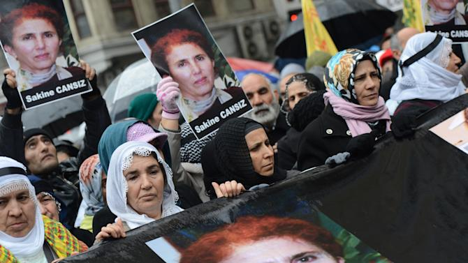 """Kurds hold photos of Sakine Cansiz, one of the founders of a militant group battling Turkish troops since 1984, as they protest against France outside the French consulate in Istanbul, Turkey, Friday, Jan. 11, 2013. Cansiz and two other women were """"executed"""" at a Kurdish center in Paris, Thursday. It was not immediately clear who killed the women, who belonged to the PKK, a group that Turkey and its Western allies, including the United States and the European Union, consider a terrorist organization. (AP Photo)"""