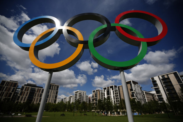 A set of Olympic rings are seen standing in front of apartments for athletes during a media opportunity at the Olympic and Paralympic athlete's village in London, Thursday, July 12, 2012. The London Olympics begin on July 27. (AP Photo/Matt Dunham)