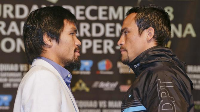 Manny Pacquiao, left, and Juan Manuel Marquez pose for photos during a news conference, Wednesday, Dec. 5, 2012, in Las Vegas. Pacquiao and Marquez are scheduled to face off in a welterweight boxing match on Saturday. (AP Photo/Julie Jacobson)