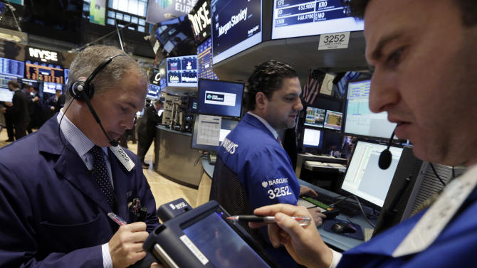 Traders gather at the post of specialist Ronnie Howard, center, on the floor of the New York Stock Exchange Monday, April 29, 2013. Enthusiasm on Wall Street sparked by another positive report on the U.S. economy helped push most Asian stock markets higher Wednesday May 15, 2013. But lower-than-expected German economic growth disappointed investors elsewhere. (AP Photo/Richard Drew)