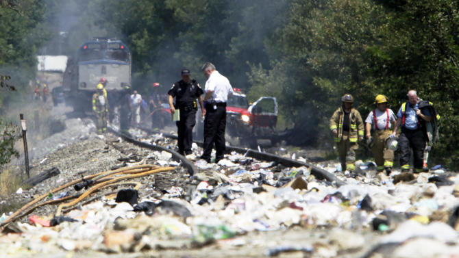 Officials survey the area around an Amtrak train, background, that collided into a tractor-trailer Monday, July 11, 2011, in North Berwick, Maine. Both were set  on fire an official said and the truck driver was killed. Some of the train's 109 passengers were injured, but it's not clear how many or how seriously they were hurt. The crash happened at about 11 a.m. in North Berwick, about 40 miles south of Portland. (AP Photo/Pat Wellenbach)