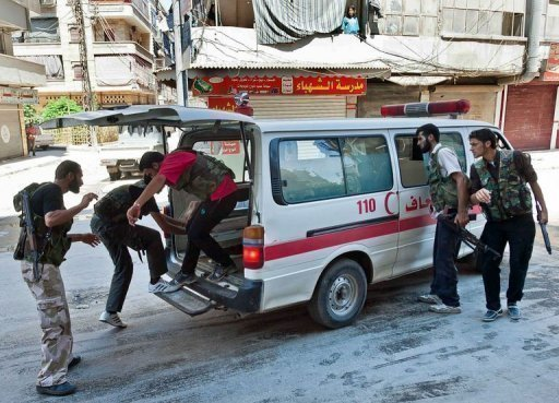 """Syrian rebel fighters load a wounded person into an ambulance during clashes with pro-regime forces in the al-Sahur district of Aleppo on August 7. Syrian rebels said a """"barbaric and savage attack"""""""