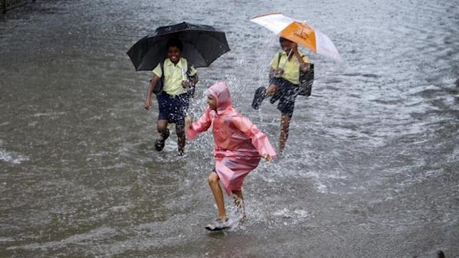 School children play on a flooded street during heavy monsoon rains in Mumbai July 23, 2013. REUTERS/Vivek Prakash/Files