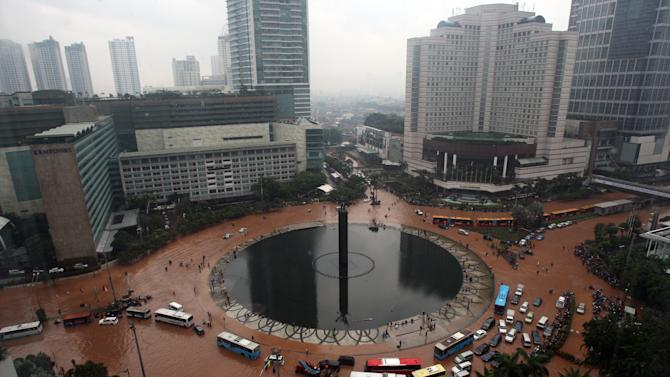 Indonesians wade through floods in Jakarta, Indonesia, Thursday, Jan. 17, 2013. Seasonal rains have triggered massive flooding in Indonesia's capital, triggering the evacuation of at least 20,000 people in Jakarta. (AP Photo/Achmad Ibrahim)