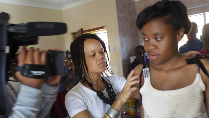 In this photograph shot Saturday May 19, 2012, 29-year-old designer Tebogo Lehlabi tries her designs on a model during rehearsal in a Johannesburg, South Africa residential neighborhood  for the Soweto  Fashion Week scheduled to start Thursday May 24, 2012. Designers and entrepreneurs who have gotten together to put on a fashion show in Soweto are inspired by the famed township's creativity and history.(AP Photo/Jerome Delay)