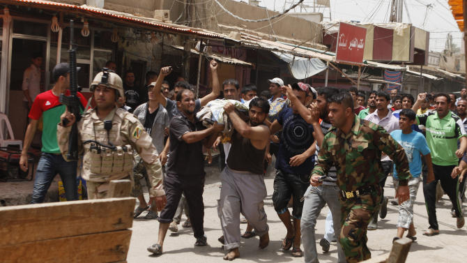 FILE - In this Thursday, June 28, 2012, file photo, people carry the body of a victim of a car bomb attack in the Washash neighborhood of Baghdad, Iraq. June was the second-deadliest month since U.S. troops withdrew from Iraq in mid-December, but more significant than the numbers was the fact that insurgents appeared able to sustain the level of violence over a longer period than usual. (AP Photo/Karim Kadim, File)