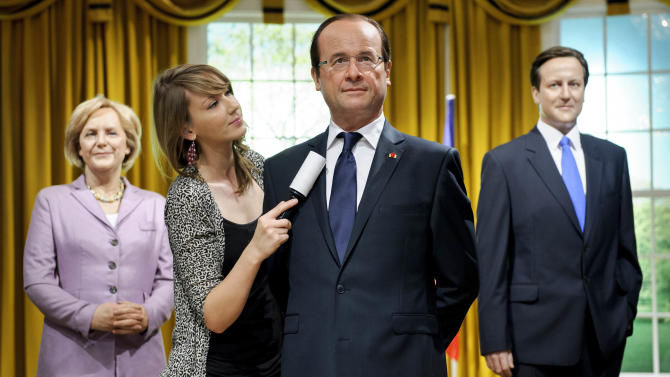 The finishing touches are applied to the wax figure of French President Francois Hollande, by Claire Galvin, surrounded by the Chancellor of Germany Angela Merkel and British Prime Minister David Cameron at Madame Tussauds, London, Thursday, Aug. 23, 2012. (AP Photo/Jonathan Short)