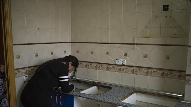 """Carolina Salazar Fernandez, 23 years old, right, accompanied by a housing rights activist, partly seen at left, covers her face ashamed of her kitchen appearance after she had removed her appliances during her eviction in Madrid, Spain, Thursday, Feb. 27, 2014. Carolina Salazar Fernandez, is a single mother of two children: Jesus, 3 years old, and Abraham, 6 years old. Her only income it is a state benefit of 530 euros ($ 723). She has occupied an empty foreclosed apartment owned by SAREB bank in February 2013. She tries to negotiate to pay a low protected rent, since her income it is not enough to rent an apartment and support the family at the same time. The eviction was finally postponed with the help of housing rights' activists. SAREB, called """"bad bank"""", is a bank who receives toxic assets produced by Spanish lenders after the country's property market collapse in 2008. (AP Photo/Andres Kudacki)"""