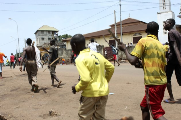 Opposition protesters carry sticks as they march along a street in Conakry