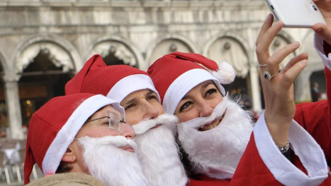 People dressed as Santa Claus pose for a selfie in Saint Mark's Square in Venice