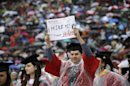 Jeffrey Canas, of Union City, holds up a sign at Rutgers University's football stadium in Piscataway, N.J., Sunday, May 19, 2013, during graduation ceremonies. (AP Photo/Mel Evans)