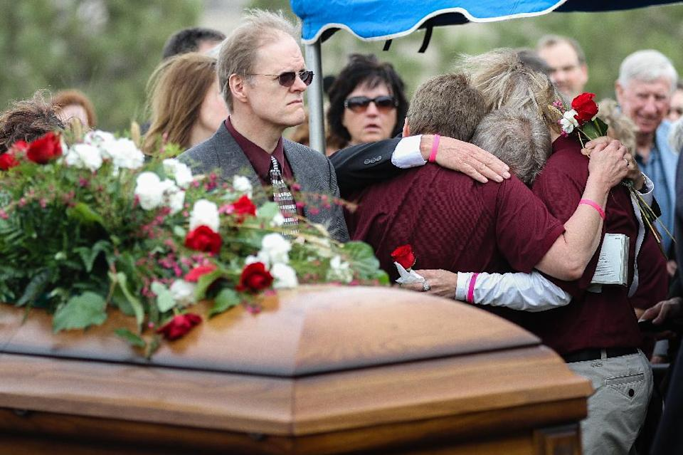 Two Sidney school teachers hug Gary Arnold during the funeral service for his late wide, Sherry Arnold, in Sidney, Mont. on Friday, March 30, 2012. Arnold, a high school teacher, was kidnapped and murdered after disappearing in January. (AP Photo/Williston Herald, Elijah Nouvelage)