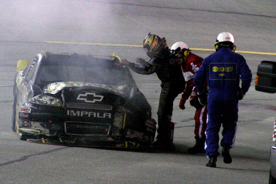 Ryan Newman exits his car near the pits after it caught fire during the NASCAR Sprint Cup Series auto race at Atlanta Motor Speedway, Sunday, Sept. 2, 2012, in Hampton, Ga. (AP Photo/Dale Davis)