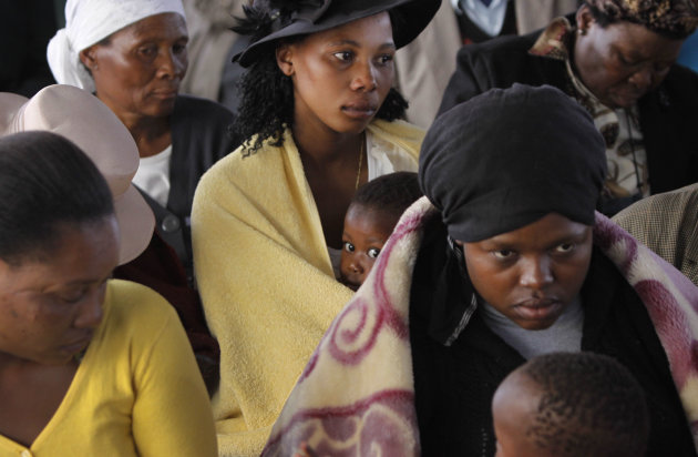 Mourners attend a memorial service at the Lonmin Platinum Mine near Rustenburg, South Africa, Thursday, Aug. 23, 2012 after police shot and killed 34 striking miners and wounded 78 last week. Demands for higher wages spread to at least two other mines, raising fears of further protests at more South African mines that provide most of the world&#39;s platinum. (AP Photo/Denis Farrell)
