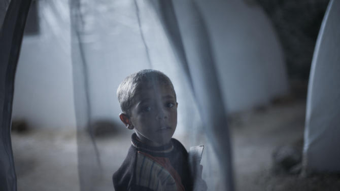 A Syrian boy, who fled his home with his family due to fighting between government forces and rebels, stands near his tent at a refugee camp near the Turkish border, in Azaz, Syria, Sunday, Oct. 7, 2012. (AP Photo/ Manu Brabo)