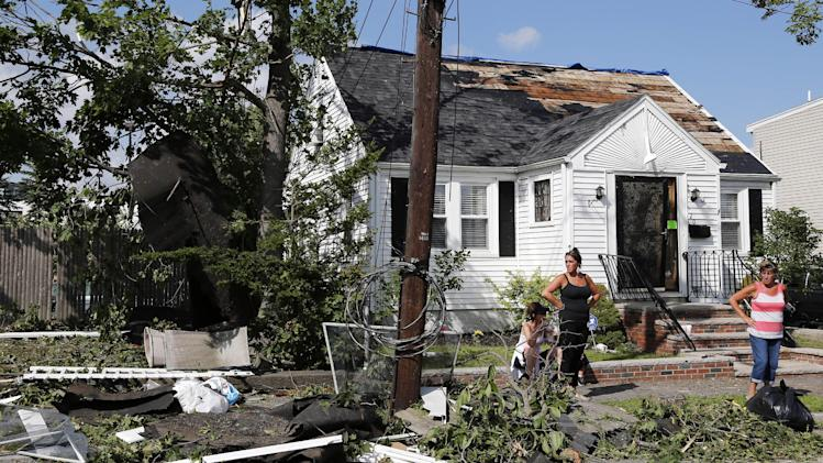 Family members stand outside their damaged house in Revere, Mass., Monday, July 28, 2014, after a tornado touched down. Revere Deputy Fire Chief Mike Viviano says the fire department in that coastal city has received dozens of calls reporting partial building and roof collapses, and downed trees and power lines. Viviano says there are no immediate reports of deaths or serious injuries. (AP Photo/Elise Amendola)