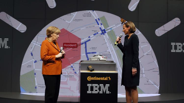 An IBM official presents a software to German Chancellor Merkel at the IBM booth during the CeBIT technology fair in Hanover