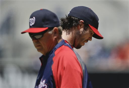 Washington Nationals starting pitcher Dan Haren stares at the ground after a visit from pitching coach Steve McCatty during the first inning in which Hren surrendered three runs to the San Diego Padre