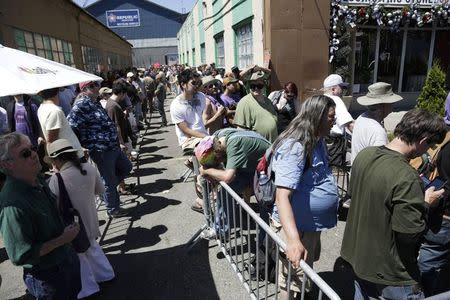 People wait in the heat to enter Cannabis City during the first day of legal retail marijuana sales in Seattle, Washington