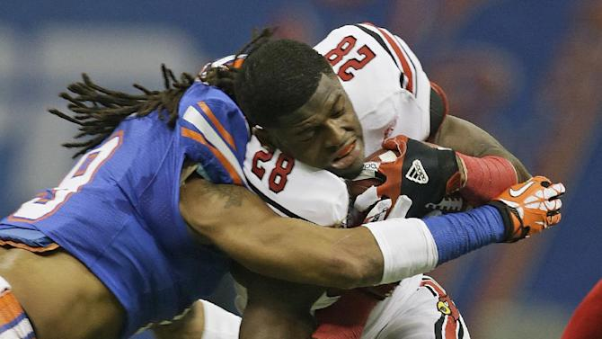 Florida defensive back Josh Evans (9) stops Louisville running back Jeremy Wright (28) after a short game and the loss of his helmet in the first quarter of the Sugar Bowl NCAA college football game Wednesday, Jan. 2, 2013, in New Orleans. (AP Photo/Dave Martin)