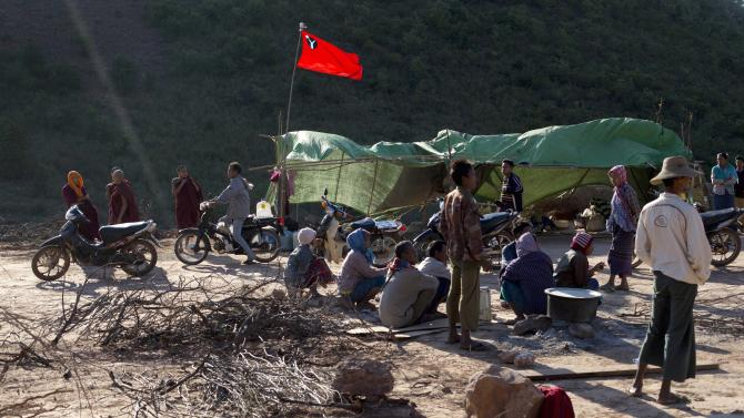 A group of protesting villages who has blocked a road with rocks and wood guard their position in Letpadaung mine, Monywa township, northwestern Myanmar, Wednesday, Nov. 28, 2012. Hundreds of Buddhist monks and villagers occupying the mine, they said is causing environmental, social and health problems, defied a government order to leave by Wednesday, saying they will stay until the project is halted. (AP Photo/Gemunu Amarasinghe)