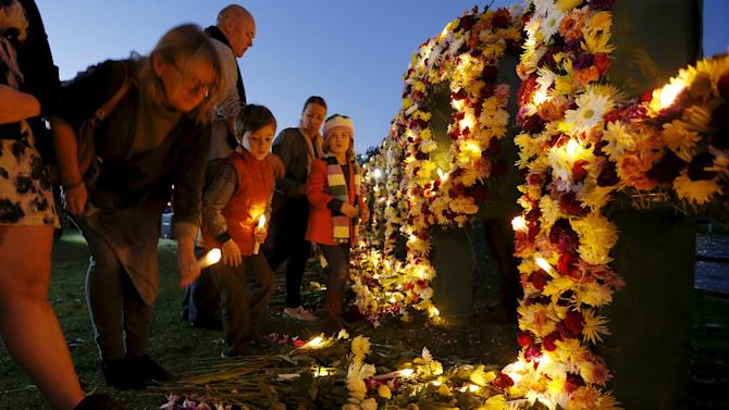 A woman places an electronic candle among flowers during a candelight vigil, calling on Indonesia to halt the planned execution of two convicted Australian drug traffickers, in Sydney