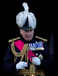 Britain&#39;s General the Lord Richard Dannatt, Constable of the Tower of London, holds the Olympic Flame after its arrival by helicopter at the Tower of London
