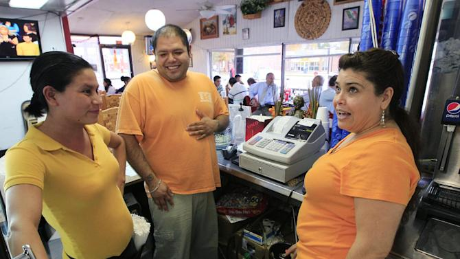In a Wednesday, Oct. 12, 2011 photo, owner Marta Guzman, right, speaks with her son, Francisco Mejia and server Maria Velazquez, left,  at Taqueria Mixteca restaurant, in Dayton, Ohio. The restaurant is one of four restaurants in southwest Ohio started and owned by the same Mexican family. It's the kind of success story that leaders in Dayton think offers hope for an entire city. It has adopted a plan not only to encourage immigrants to come and feel welcome, but also to use them to help pull out of an economic tailspin.  (AP Photo/Al Behrman)