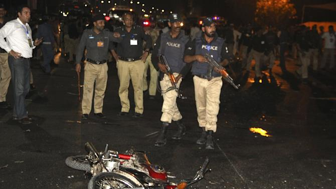 Police inspect the site of a blast that occurred during the cricket match between Pakistan and Zimbabwe, near Gaddafi Stadium in Lahore, Pakistan