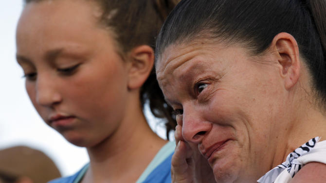 """Renee Pacheco, right, from Albacqure, N.M., wipes a tear from her face, Sunday, July 22, 2012, in Aurora, Colo., during a prayer vigil for the victims of Friday's mass shooting at a movie theater. Twelve people were killed and dozens were injured in a shooting attack early Friday at the packed theater during a showing of the Batman movie, """"The Dark Knight Rises."""" Police have identified the suspected shooter as James Holmes, 24. (AP Photo/Alex Brandon)"""
